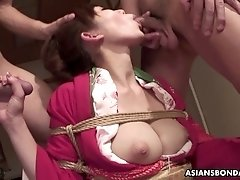 Tied up Asian bimbo sucks two cocks and gets to