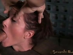 Submissive brunette fixed to the stocks gets mouthfucked by black bloke