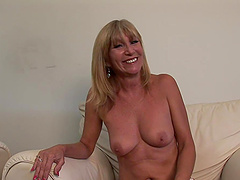 Mature pornstar with natural tits shows off her shaved pussy close up backstage
